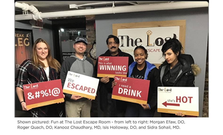 Several family medicine residents pose with signs at the Lost Escape Room.