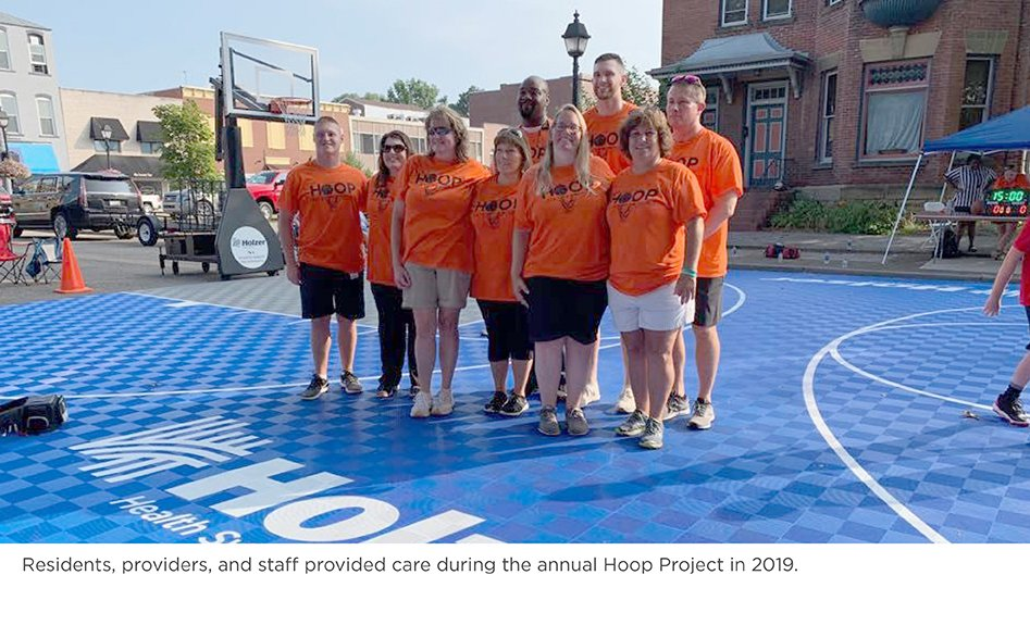 Residents, providers, and staff pose for a photo on the Holzer basketball court during the annual Hoop Project in 2019.