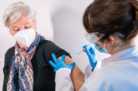 Woman receives vaccine from nurse
